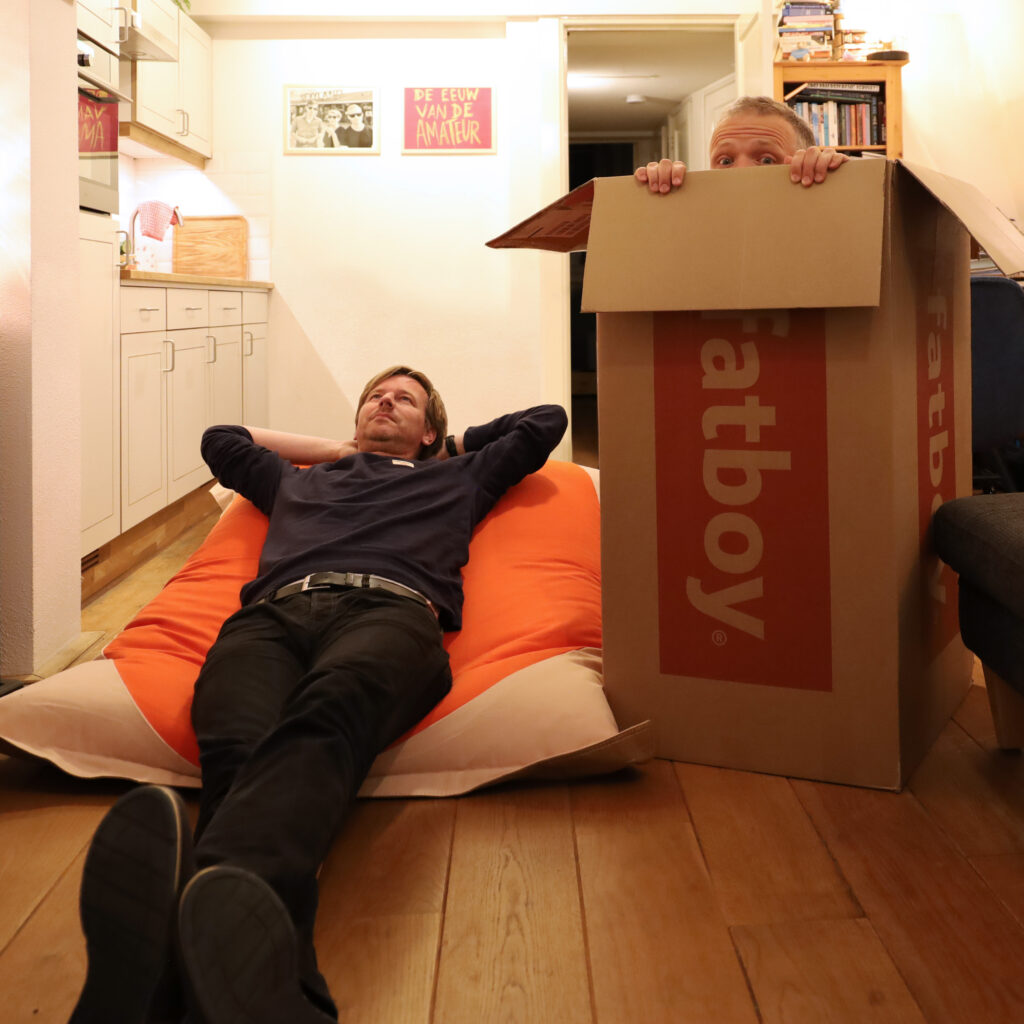 Foto met links Botte die ligt op een rode Fatboy-zitzak en rechts Ype die in de doos zit waar de zitzak uit kwam, en net met zijn ogen boven de rand uit komt.